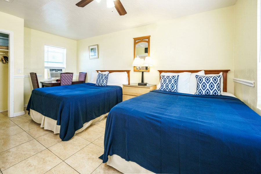 two beds with blue comforters